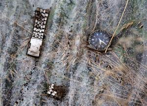 A watch and a part of bracelet lie on a plastic cover at the site of a crashed Malaysia Airlines passenger plane near the village of Rozsypne, Ukraine, eastern Ukraine Friday, July 18, 2014. Rescue workers, policemen and even off-duty coal miners were combing a sprawling area in eastern Ukraine near the Russian border where the Malaysian plane ended up in burning pieces Thursday, killing all 298 aboard. (AP Photo/Dmitry Lovetsky)