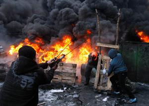 Protesters use a large slingshot to hurl rocks at police in central Kiev, Ukraine, Thursday, Jan. 23, 2014. Thick black smoke from burning tires engulfed the downtown Ukrainian capital as an ultimatum issued by the opposition to the president to call early election or face street rage was set to expire with no sign of a compromise. (AP Photo/Darko Vojinovic)