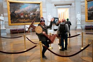 WASHINGTON, DC - JANUARY 06:  A pro-Trump protester carries the lectern of U.S. Speaker of the House Nancy Pelosi through the Roturnda of the U.S. Capitol Building after a pro-Trump mob stormed the building on January 06, 2021 in Washington, DC. Congress held a joint session today to ratify President-elect Joe Biden's 306-232 Electoral College win over President Donald Trump. A group of Republican senators said they would reject the Electoral College votes of several states unless Congress appointed a commission to audit the election results. (Photo by Win McNamee/Getty Images)