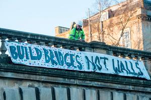 "BATH, ENGLAND - JANUARY 20:  A man stops to look at a banner reading ""Build bridges not walls"" that has been displayed on a bridge on North Parade on January 20, 2017 in Bath, England. The banner drop in Bath is part of a series of events across the world aimed at expressing disproval at today's inauguration of Donald Trump as the 45th U.S. president.  (Photo by Matt Cardy/Getty Images)"