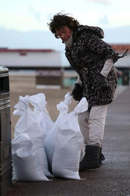 GREAT YARMOUTH, ENGLAND, DECEMBER 05:  A local resident fills sandbags on the beach on December 5, 2013 in Great Yarmouth, England. Thousands of people are being evacuated from their homes, the Environment Agency has given 42 severe floods warnings as a storm surge hits large parts of the UK. (Photo by Stephen Pond/Getty Images)