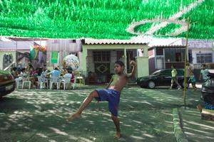 A boy plays football on Rua Santa Isabel which is covered with colourful streamers to celebrate the FIFA World Cup on June 15, 2014 in Manaus, Brazil. Group D team England lost 2-1 to Italy in their opening match of the 2014 FIFA World Cup in Manaus on June 14, 2014. (Photo by Oli Scarff/Getty Images)
