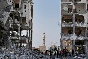 Backdropped by the damaged minaret of the Al-Azba mosque, Palestinians inspect the damage to the Nada Towers residential neighborhood in the town of Beit Lahiya, northern Gaza Strip, Tuesday, Aug. 5, 2014. (AP Photo/Lefteris Pitarakis)