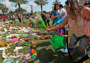 Celeste Gonzalez, 18, of Ocoee, Fla., brings a bouquet of flowers to  a memorial at Dr. Phillips Center, Monday, June 13, 2016 , in Orlando, Fla, for the victims of a shooting at the Pulse nightclub. (Red Huber/Orlando Sentinel via AP)