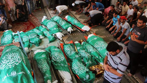 Palestinians pray over the bodies of 17 members of the Abu Jamea family, killed by an Israeli strike at their house, during their funeral at the main mosque in Khan Younis, in the southern Gaza Strip, Monday, July 21, 2014.  (AP Photo/Hatem Ali)