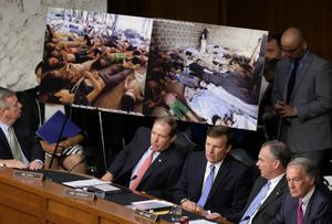 "WASHINGTON, DC - SEPTEMBER 03:  U.S. Senators view photographs of victims of chemical weapons attacks in Syria as U.S. Secretary of State John Kerry, U.S. Defense Secretary Chuck Hagel, and U.S. Chairman of the Joint Chiefs of Staff Gen. Martin Dempsey testify before the Senate Foreign Relations Committee on the topic of  ""The Authorization of Use of Force in Syria"" September 3, 2013 in Washington, DC. U.S. President Barack Obama is attempting to enlist the support of members of the U.S. Congress for military action against the Syrian government for using chemical weapons against its own people last month.  (Photo by Chip Somodevilla/Getty Images)"