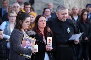 Widow Joanne McGibbon (centre) with her daughter Seana and Fr Gary Donegan joins members of the public at a vigil in the grounds of Holy Cross Church, Ardoyne. Photo by Kelvin Boyes / Press Eye.