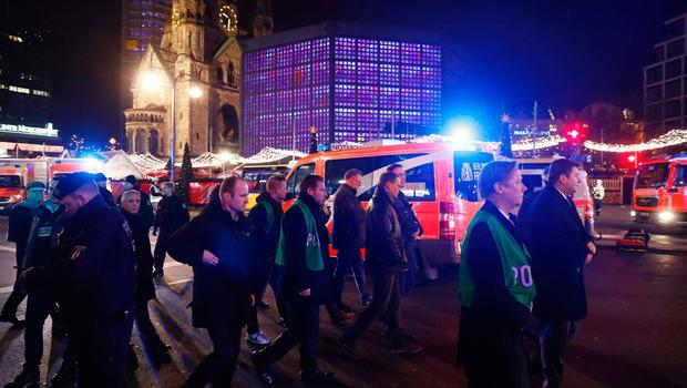 Berlin's mayor Michael Mueller (4R) walks at the site where a truck speeded into a christmas market in Berlin, on December 19, 2016 killing nine persons and injuring at least 50 people. / AFP PHOTO / Odd ANDERSENODD ANDERSEN/AFP/Getty Images