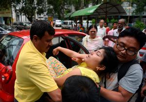 Indian hospital staff and bystanders attend to a resident who fainted as a tremor struck at Siliguri Hospital in Siliguri on May 12, 2015.   A new earthquake of 7.3-magnitude and several powerful aftershocks hit devastated Nepal on May 12, killing at least four people and sending terrified residents running into the streets of the traumatised capital. The quake was felt as far away as New Delhi, and officials said it caused buildings to collapse in Chinese-controlled Tibet.  AFP PHOTO/Diptendu DUTTADIPTENDU DUTTA/AFP/Getty Images