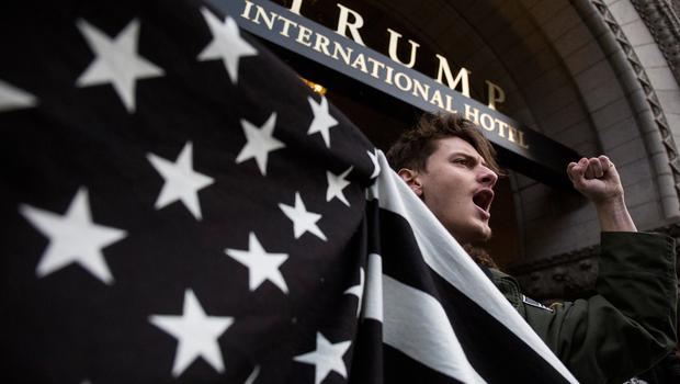 WASHINGTON, DC - JANUARY 29: John Alfonso holds a black and white American flag during a protest in front of the Trump International Hotel Washington on January 29, 2017 in Washington, DC. Protestors in Washington and around the country gathered to protest President Donald Trump's executive order barring the citizens of Muslim-majority countries Iraq, Syria, Iran, Sudan, Libya, Somalia and Yemen from traveling to the United States.  (Photo by Zach Gibson/Getty Images)