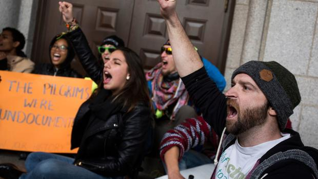 WASHINGTON, DC - JANUARY 29: Demonstrators chant outside of the Trump Hotel International during a protest on January 29, 2017 in Washington, DC. Protestors in Washington and around the country gathered to protest President Donald Trump's executive order barring the citizens of Muslim-majority countries Iraq, Syria, Iran, Sudan, Libya, Somalia and Yemen from traveling to the United States.  (Photo by Zach Gibson/Getty Images)