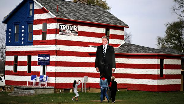 A young visitor takes a photo of a giant cutout of Republican candidate for president Donald Trump in front of the Trump House owned by Lisa Rossi in Youngstown, Pa, Tuesday, Nov. 8, 2016. (AP Photo/Gene J. Puskar)