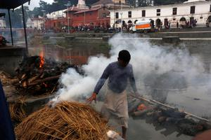 A hindu priest lights the funeral pyre of a victim of Saturday's earthquake, at the Pashupatinath temple, on the banks of Bagmati river, in Kathmandu, Nepal, Monday, April 27, 2015.  A strong magnitude earthquake shook Nepals capital and the densely populated Kathmandu valley on Saturday devastating the region and leaving some tens of thousands shell-shocked and sleeping in streets.  (AP Photo / Manish Swarup)