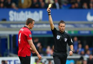 LIVERPOOL, ENGLAND - APRIL 20:  Referee Mark Clattenburg shows Phil Jones of Manchester United a yellow card for handball during the Barclays Premier League match between Everton and Manchester United at Goodison Park on April 20, 2014 in Liverpool, England.  (Photo by Alex Livesey/Getty Images)