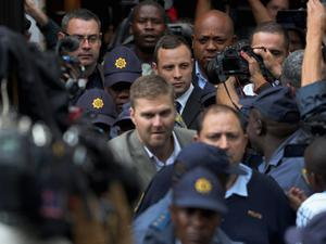 Oscar Pistorius (C) leaves North Gauteng High Court amid a media scrum after the second day of his trial accused of the murder of his girlfriend Reeva Steenkamp on March 4, 2014 in Pretoria, South Africa. (Photo by Christopher Furlong/Getty Images)