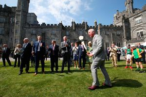 The Prince of Wales tries his hand at hurling as he and the Duchess of Cornwall visit Kilkenny Castle. PA
