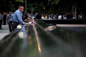 NEW YORK, NY - SEPTEMBER 11:  A man stands in a moment of silence at the 9-11 Memorial site on September 11, 2015 in New York City. Today marks the 14th anniversary of the attacks where nearly 3,000 people were killed in New York, Washington D.C. and Pennsylvania.  (Photo by Andrew Burton/Getty Images)