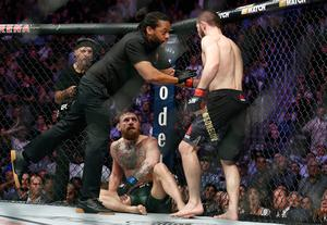 Khabib Nurmagomedov, right, is held back by referee Herb Dean after fighting Conor McGregor, bottom, during a lightweight title mixed martial arts bout at UFC 229 in Las Vegas, Saturday, Oct. 6, 2018. Nurmagomedov won the fight by submission during the fourth round to retain the title. (AP Photo/John Locher)