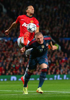 MANCHESTER, ENGLAND - APRIL 01:  Rio Ferdinand of Manchester United and Bastian Schweinsteiger of Bayern Muenchen battle for the ball during the UEFA Champions League Quarter Final first leg match between Manchester United and FC Bayern Muenchen at Old Trafford on April 1, 2014 in Manchester, England.  (Photo by Alex Livesey/Getty Images)