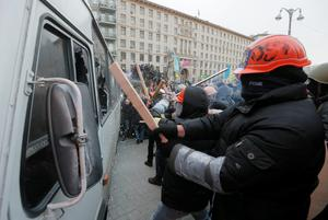 Protesters attack a riot police bus in central Kiev, Ukraine, Sunday, Jan. 19, 2014. Hundreds of protesters on Sunday clashed with riot police in the center of the Ukrainian capital, after the passage of harsh anti-protest legislation last week seen as part of attempts to quash anti-government demonstrations. A group of radical activists began attacking riot police with sticks, trying to push their way toward the Ukrainian parliament building, which has been cordoned off by rows of police and buses. (AP Photo / Efrem Lukatsky)