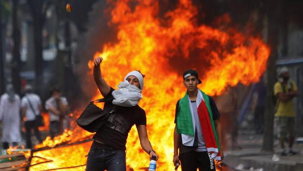 A pro-Palestinian demonstrator throws a stone towards riot police, during a demonstration in Paris, Saturday, July 19, 2014.  (AP Photo/Thibault Camus)