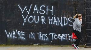 A woman walks past graffiti calling on people to wash their hands during the Covid-19 crisis in east Belfast (Niall Carson/PA)