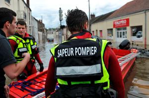 Firefighters stand by their boat as the city is flooded due to heavy rainfalls at Montargis, central France, on June 01, 2016.  Torrential downpours have lashed parts of northern Europe in recent days, leaving four dead in Germany, breaching the banks of the Seine in Paris and flooding rural roads and villages.  / AFP PHOTO / GUILLAUME SOUVANTGUILLAUME SOUVANT/AFP/Getty Images