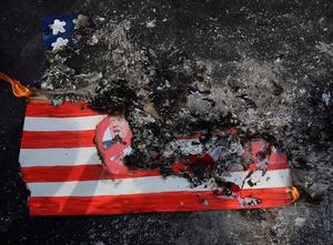 Activists burn a mock US flag with President-elect Donald Trump's portrait during a rally in front of the US embassy in Manila on January 20, 2017, ahead of Trump's presidential inauguration. AFP/Getty Images