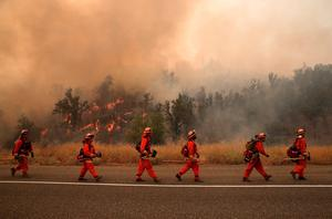 CLEARLAKE, CA - AUGUST 02: Inmate firefighters march along highway 20 as they monitor a burn operation to head off the Rocky Fire on August 2, 2015 near Clearlake, California. Over 1,900 firefighters are battling the Rocky Fire that has burned over 46,000 acres since it started on Wednesday afternoon. The fire is currently five percent contained and has destroyed at least 14 homes. (Photo by Justin Sullivan/Getty Images)