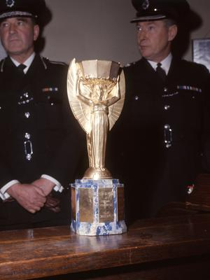 Police officers with the recovered World Cup trophy (PA)