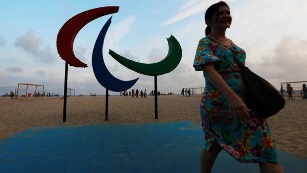 RIO DE JANEIRO, BRAZIL - SEPTEMBER 05:  A woman walks in front of the Paralympic symbol, Agitos, on Copacabana beach ahead of the Rio 2016 Paralympic Games on September 5, 2016 in Rio de Janeiro, Brazil.  (Photo by Mario Tama/Getty Images)