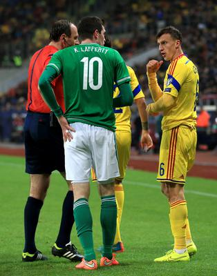 Northern Ireland's Kyle Lafferty (left) argues with Romania's Vlad Chiriches during the UEFA Euro 2016 qualifier at the Arena Nationala, Bucharest. Nick Potts/PA Wire.
