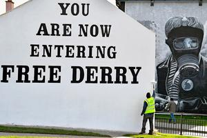 A man paints the 'Free Derry' corner wall in the Bogside ahead of the Funeral of Martin McGuinness. (Photo by Jeff J Mitchell/Getty Images)