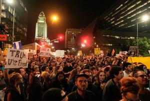 """Demonstrators gather to protest a day after President-elect Donald Trump's victory, at a rally outside Los Angeles City Hall in Los Angeles, California, on November 9, 2016.GO Protesters burned a giant orange-haired head of Donald Trump in effigy, lit fires ins the streets and blocked traffic lanes late on November 9 as rage over the billionaire's election victory spilled onto the streets of US cities. From New York to Los Angeles, thousands of people in around 10 cities rallied against the president-elect a day after his stunning win, some carrying signs declaiming """"Not our President"""" and """"Love trumps hate."""" / AFP PHOTO / RINGO CHIURINGO CHIU/AFP/Getty Images"""