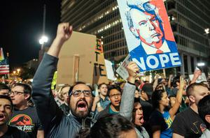 """Demonstrators hold up placards to protest a day after President-elect Donald Trump's victory, during a rally outside Los Angeles City Hall in Los Angeles, California, on November 9, 2016. Protesters burned a giant orange-haired head of Donald Trump in effigy, lit fires ins the streets and blocked traffic lanes late on November 9 as rage over the billionaire's election victory spilled onto the streets of US cities. From New York to Los Angeles, thousands of people in around 10 cities rallied against the president-elect a day after his stunning win, some carrying signs declaiming """"Not our President"""" and """"Love trumps hate."""" / AFP PHOTO / RINGO CHIURINGO CHIU/AFP/Getty Images"""