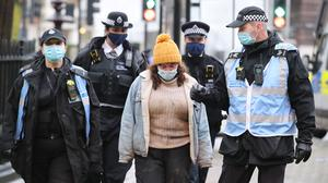 Police officers escort a protester who had been stood on top of a lorry blocking traffic near to the encampment in Euston Square Gardens in central London (Aaron Chown/PA)