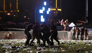 People carry a person at the Route 91 Harvest country music festival after apparent gun fire was heard on October 1, 2017 in Las Vegas, Nevada. There are reports of an active shooter around the Mandalay Bay Resort and Casino.  (Photo by David Becker/Getty Images)