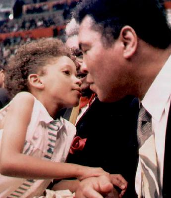 """This file photo taken on December 16, 1994 shows Legendary US boxer Muhammad Ali is kissed by a young Ecuadoran girl at the Quito's Ruminahui Coliseum, Ecuador.  Boxing icon Muhammad Ali died on Friday, June 3, a family spokesman said in a statement. """"After a 32-year battle with Parkinsons disease, Muhammad Ali has passed away at the age of 74,"""" spokesman Bob Gunnell said.  / AFP PHOTO / Fernando AraujoFERNANDO ARAUJO/AFP/Getty Images"""