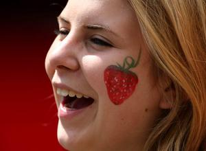 LONDON, ENGLAND - JUNE 25:  A spectator laughs with a strawberry painted on her face during day two of the Wimbledon Lawn Tennis Championships at the All England Lawn Tennis and Croquet Club on June 25, 2013 in London, England.  (Photo by Dan Kitwood/Getty Images)