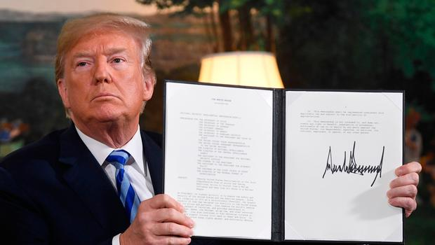 US President Donald Trump signs a document reinstating sanctions against Iran after announcing the US withdrawal from the Iran Nuclear deal, in the Diplomatic Reception Room at the White House in Washington, DC, on May 8, 2018. / AFP PHOTO / SAUL LOEBSAUL LOEB/AFP/Getty Images