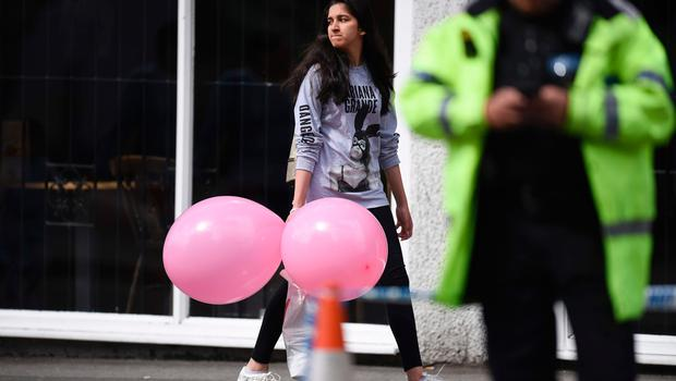 A  girl wearing a t-shirt of US singer Ariana Grande carrying balloons from the Ariana Grande concert