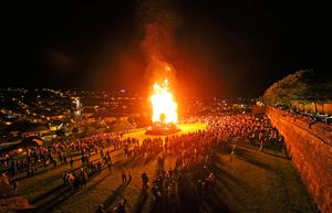 People watch a bonfire in the bogside area of Londonderry, which is traditionally torched on August 15 to mark a Catholic feast day celebrating the assumption of the Virgin Mary into heaven, but in modern times the fire has become a source of contention and associated with anti-social behaviour. PRESS ASSOCIATION Photo. Picture date: Tuesday August 15, 2017. Disorder flared in Londonderry on Monday night as bonfire-builders attacked police and members of the public. Police said those gathered at the controversial fire site in Derry's Bogside threw rocks and stones at local people before targeting police with petrol bombs and other missiles. See PA story ULSTER Bonfire. Photo credit should read: Niall Carson/PA Wire