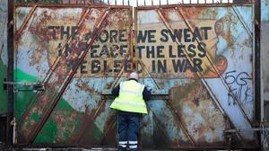 A council worker closes the gate on the Lanark way interface gate in west Belfast after rioting the night before (Press Eye).