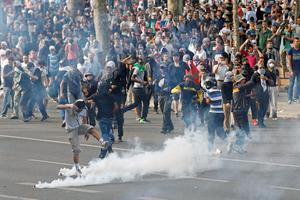 Pro-Palestinian protesters run amid tear gas canisters, as clashes erupted at Place de La Republique during a banned demonstration in support of Gaza, in Paris, France, Saturday, July 26, 2014 (AP Photo/Francois Mori )