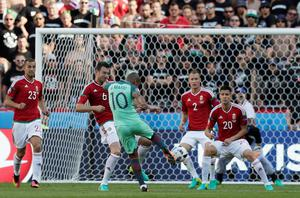 Portugal's Joao Mario, center, attempts a shot at goal during the Euro 2016 Group F soccer match between Hungary and Portugal at the Grand Stade in Decines-Charpieu, near Lyon, France, Wednesday, June 22, 2016. (AP Photo/Pavel Golovkin)