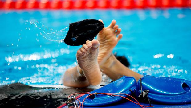 Tomotaro Nakamura of Japan removes his swim cap with his feet while training in the Olympic Aquatics Stadium during the Paralympic Games in Rio de Janeiro, Brazil, on September 6, 2016. Photo by: Simon Bruty for OIS/IOC via AFP. RESTRICTED TO EDITORIAL USE. / AFP PHOTO / OIS/IOC / Simon Bruty for OISSIMON BRUTY FOR OIS/AFP/Getty Images