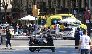 Injured people are treated in Barcelona, Spain, Thursday, Aug. 17, 2017 after a white van jumped the sidewalk in the historic Las Ramblas district, crashing into a summer crowd of residents and tourists and injuring several people, police said. (AP Photo/Oriol Duran)