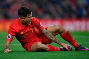 Liverpool's Brazilian midfielder Philippe Coutinho holds his foot as he lies on the pitch injured during the English Premier League football match between Liverpool and Sunderland at Anfield in Liverpool, north west England on November 26, 2016. AFP/Getty Images