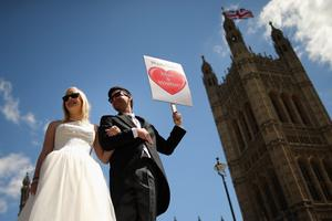 LONDON, ENGLAND - JUNE 03:  Proponents of single sex marriage dressed as a bride and groom, Carrie Hardy, and Martin Etchart of Argentina, stand outside the Houses of Parliament on June 3, 2013 in London, England. A government bill allowing same sex marriage in England and Wales was passed in the House of Commons last month, despite the opposition of 133 Conservative MP's. The bill will be debated later today in the House of Lords.  (Photo by Dan Kitwood/Getty Images)