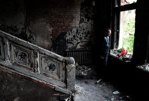 A man lays flowers inside the burnt trade union building in Odessa, Ukraine, Sunday, May 4, 2014. More than 40 people died in the riots, which some from gunshot wounds, but most in a horrific fire that tore through the trade union building late Friday. (AP Photo/Sergei Poliakov)